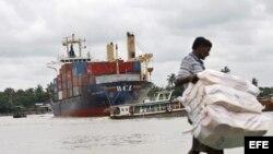 Un trabajador birmano descarga sacos de arroz de un barco en el muelle de Rangún, en Birmania.