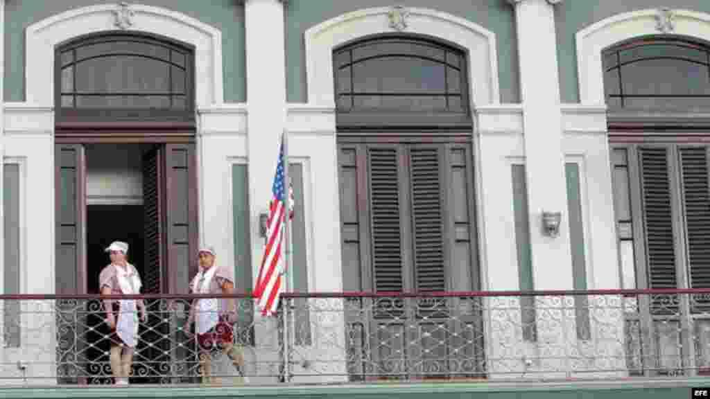 Empleadas acomodan bandera estadounidense en hotel donde llegó una comitiva de senadores de EE.UU.