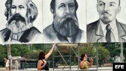 Dos turistas posan junto a carteles con los rostros de Marx, Engels y Lenin en la Plaza de la Revolución de La Habana.