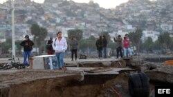 Un grupo de personas observa los destrozos causados por el tsunami posterior al terremoto de magnitud 8,4 en el puerto de Coquimbo (Chile).