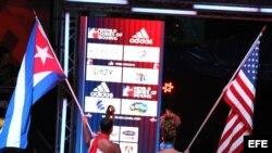 """Dos mujeres caminan con las banderas de Cuba y Estados Unidos al comienzo del enfrentamiento entre el equipo """"Domadores de Cuba"""" y USA knockouts por la Serie Mundial de boxeo."""