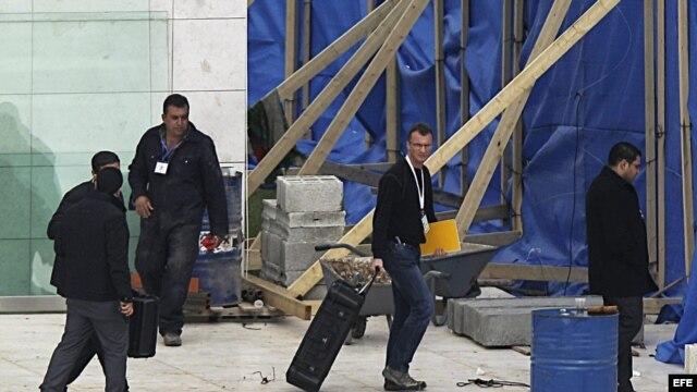 Un hombre (2º dcha), que pudiera ser uno de los investigadores internacionales, carga con una maleta en el mausoleo de Yaser Arafat en Ramala (Cisjordania).