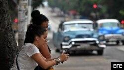 Dos mujeres navegan por internet usando una red wifi en La Habana (Cuba). Aechivo.
