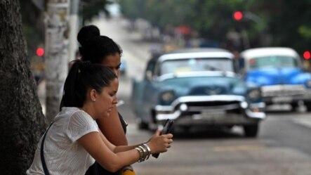 Dos mujeres navegan por internet usando una red Wi-Fi en La Habana.