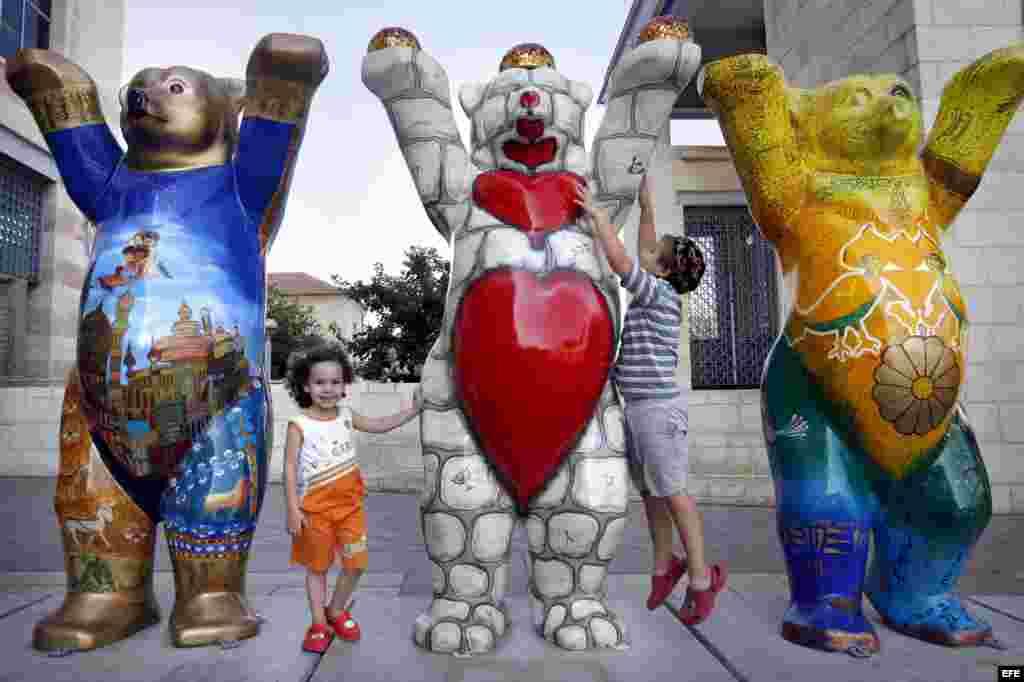 """Dos niños israelíes juegan junto al """"Oso Amigo"""" israelí y al """"Oso amigo"""" iraní en la exhibición de los 'United Buddy Bears 2007' (""""Amigos Osos Unidos"""") situada cerca del Ayuntamiento de Jerusalén, en Israel, en el 2007."""