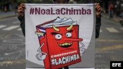 Un hombre sostiene un cartel con una caricatura que representa la Constituyente convocada por Nicolás Maduro.