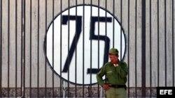ARCHIVO. Un soldado cubano monta guardia junto a la Oficina de Intereses de Estados Unidos en Cuba, donde se colocó un cartel con un número 75 en solidaridad con los 75 disidentes detenidos en la primavera del 2003.