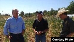 El gobernador de Missouri Jay Nixon (i) visita una granja del Estado afectada por la sequía y el calor.