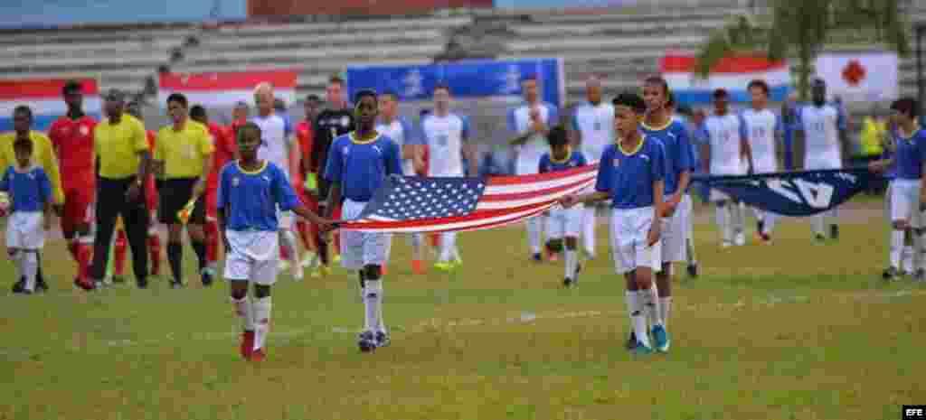 Niños deportistas portan la bandera de EE.UU., en el Estadio Pedro Marrero en La Habana, el 7 de octubre de 2016, durante la inauguración del partido amistoso de fútbol entre Cuba y Estados Unidos.