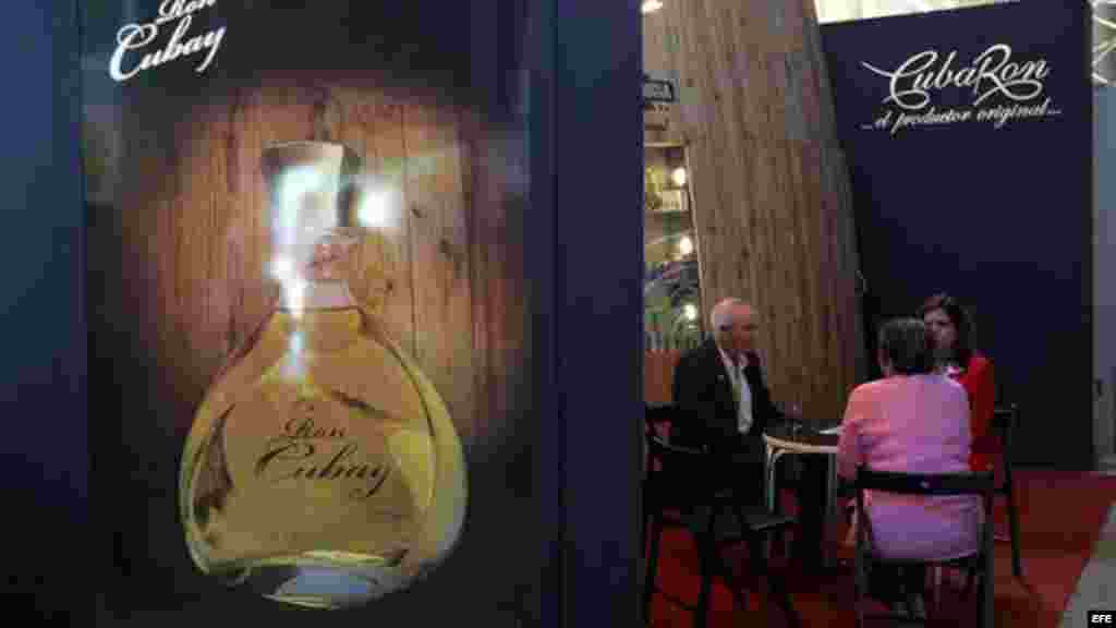Un grupo de personas habla el stand del fabricante cubano de licores Cuba Ron