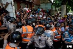 Miembros de la Policía Nacional Bolivariana contienen a un grupo de personas que trata de ingresar a un supermercado donde se venden dos kilos de pasta por persona.