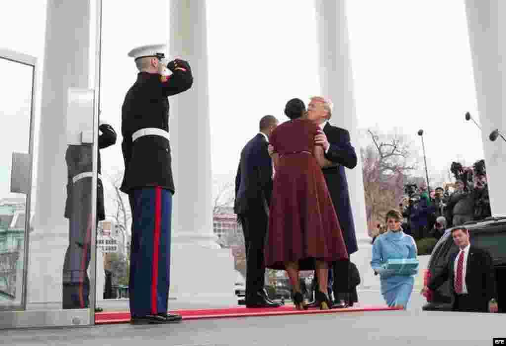 La primera dama Michelle Obama (c) besa al presidente electo, Donald Trump (d), a su llegada a la Casa Blanca.