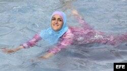 """Una mujer turca se baña con un """"burkini"""" en Alemania."""