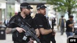 Agentes de policía británicos permanecen en guardia en el centro de Manchester, Reino Unido.