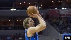 Dirk Nowitzki (i) de los Dallas Mavericks se dispone a lanzar la bola…