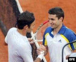 Federer (i) y Simon (d) estrechan manos tras concluir el partido.