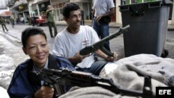 """Archivo - Dos civiles permanecen atrincherados, ella con un fusil AKM y él con uno de utilería, en un n """"enfrentamiento con el enemigo"""" en Centro Habana, el Día Nacional de la Defensa de Cuba."""