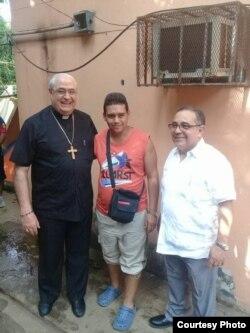 El cardenal José Luis Lacunza (derecha) y Víctor Luis Berrío, de Cáritas Panamá (izquierda) junto a uno de los migrantes cubanos.