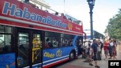 Turistas abordan un autobús turístico en La Habana (Cuba).