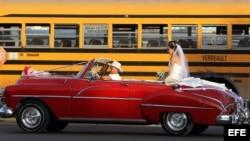 Una pareja de recién casados viaja en un viejo auto descapotable en La Habana (Cuba).