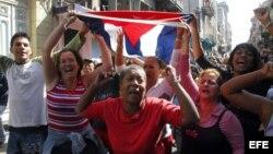 impatizantes del Gobierno cubano gritan consignas revolucionarias mientras el grupo de mujeres Las Damas de Blanco.