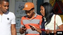 Jóvenes utilizan sus teléfonos celulares en Cuba (Archivo)