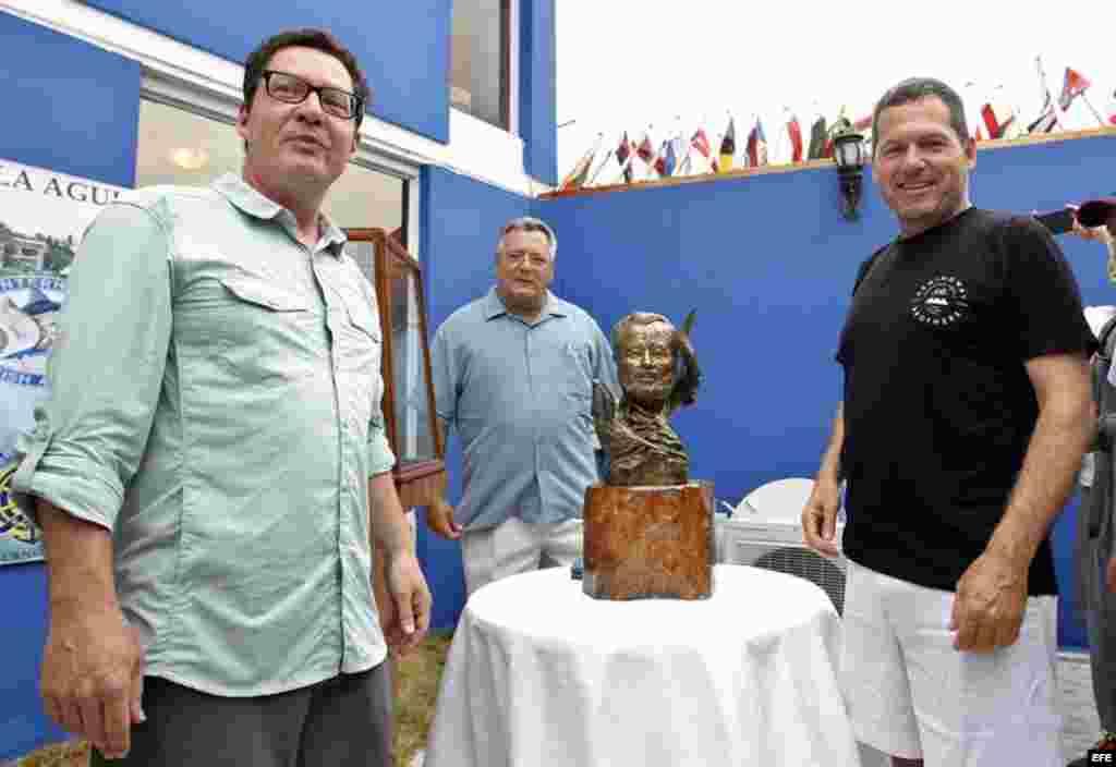 John (d) y Patrick Hemingway (i), nietos de Ernest Hemingway, participan junto al comodoro del Club Náutico Internacional Marina Hemingway, Jose Migues Scrich (c), en la develación del busto de su abuelo.
