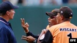 Fotografía de archivo. Víctor Mesa (c) es aguantado por el entrenador de lanzamiento de su equipo, mientras discute con el árbitro principal durante un juego en el estadio Latinoamericano de La Habana, Cuba.