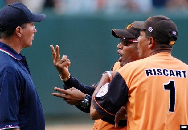 El director técnico de Villa Clara, Víctor Mesa (c) es aguantado por el entrenador de pitcheo de su equipo, José Ramón Riscart (d) mientras discute con el árbitro principal Pedro Morgado (i.) durante un partido en el estadio Latinoamericano.