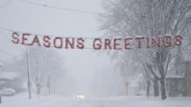 """Un letrero de """"Felices Fiestas"""" es cubierto por la nieve en una calle de Beaver Dam, estado de Wisconsin (EEUU)."""