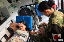 Una soldado brinda atención médica a una mujer que resultó herida durante la avalancha.