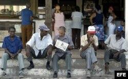 Un grupo de ancianos conversan sentados en un muro mientras esperan la llegada del periódico.
