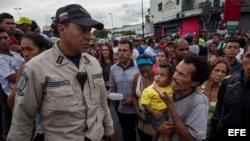 Un hombre con un niño en brazos grita consignas a un miembro de la Policía Nacional Bolivariana (PNB), durante una protesta para exigir alimentos en el sector popular Catia, en Caracas (Venezuela).
