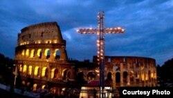 Una enorme cruz iluminada con velas se recorta contra las ruinas del Coliseo romano durante el via crucis nocturno del Viernes Santo de 2014