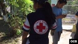 Una asistente de la Cruz Roja de Costa Rica ayuda a migrantes cubanos en un albergue temporal de La Cruz. Foto: Claudio Castillo, Martí Noticias.