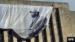 Un obrero despliega un lienzo con la imagen del fallecido líder cubano Fidel Castro en la Plaza de la Revolución .