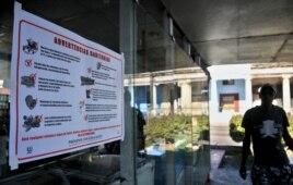 Un hombre pasa junto a un cartel alusivo al control sanitario