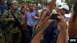 Un grupo de indígenas rodea a un guerrillero de las FARC en la vía que conduce de El Palo a Toribío.