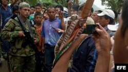 Un grupo de indígenas rodea a un guerrillero de las FARC en la vía que conduce de El Palo a Toribio.