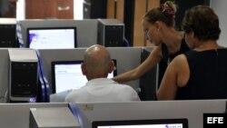 Varias personas se conectan a internet desde una sala de navegación en La Habana.