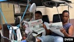 Dos bicitaxistas leen el Granma, en La Habana, Cuba.