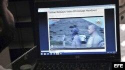 Un hombre observa en una pantalla de ordenador el vídeo difundido por los talibanes que muestra el momento en el que los insurgentes liberan al soldado Bowe Bergdahl (2d).