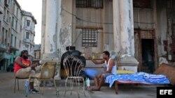 Dos hombres cuyas viviendas fueron severamente afectadas por el huracán Irma conversan junto a sus pertenencias, el jueves 21 de septiembre de 2017, en el malecón de La Habana (Cuba).