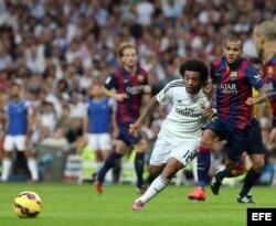 El defensa brasileño del Real Madrid Marcelo Vieira (i) lucha la posición con su compatriota del FC Barcelona Dani Alves.