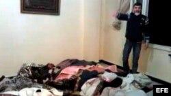 Un hombre de pie junto a los cadávares de varias personas que él denuncia fueron asesinadas por el ejército sirio en Homs (Siria).