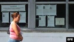 Una mujer camina junto a carteles alusivos a las elecciones municipales en Cuba. (Archivo)