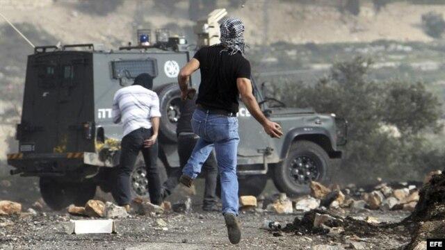 Palestinos lanzan piedras a un vehículo policial israelí durante un protesta contra el asentamiento judío de Kedumim, en Cisjordania.