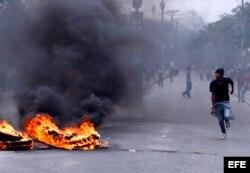 Manifestantes pasan junto a una barricada durante la marcha organizada por la oposición en Puerto Príncipe, Haití.