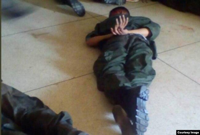 Un militar sublevado yace reducido en el piso.
