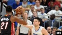 El jugador de Magic Nikola Vucevic (d) marca a Hassan Whiteside (i), del Heat.
